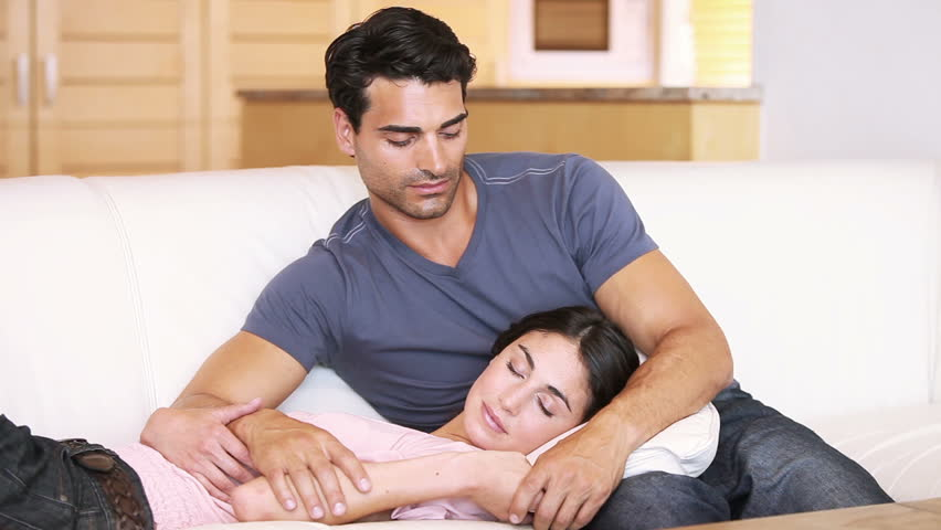 Young man looking at his sleeping girlfriend while sitting on the couch | Shutterstock HD Video #2323610