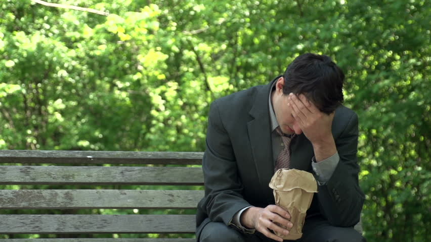 Depressed business man drinking booze from a bag at the park - HD stock footage clip