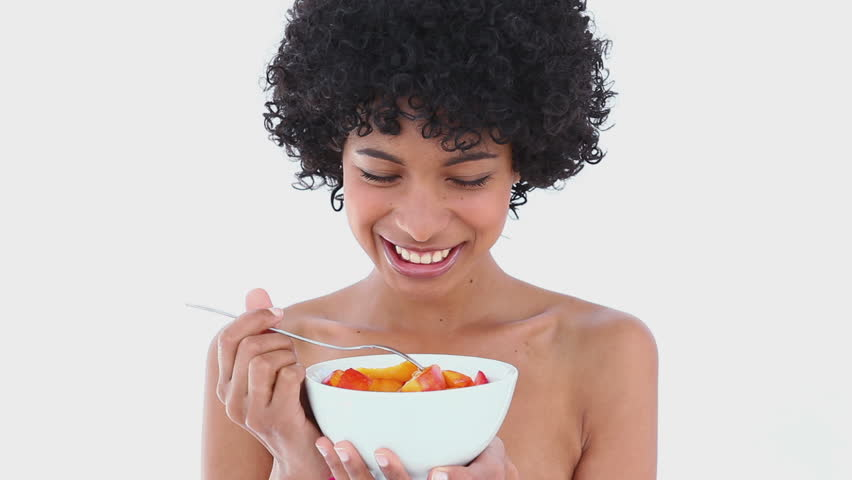 Smiling woman eating a fruit salad against white background - HD stock video clip