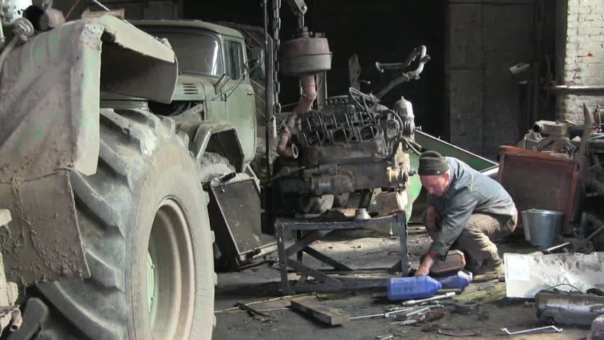 An auto mechanic works with old car - HD stock footage clip