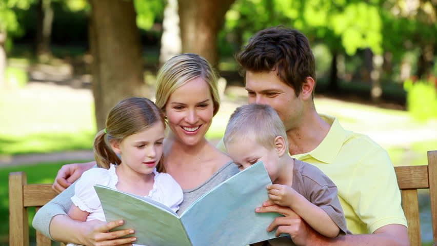 Family looking a picture book on a bench in a park - HD stock video clip