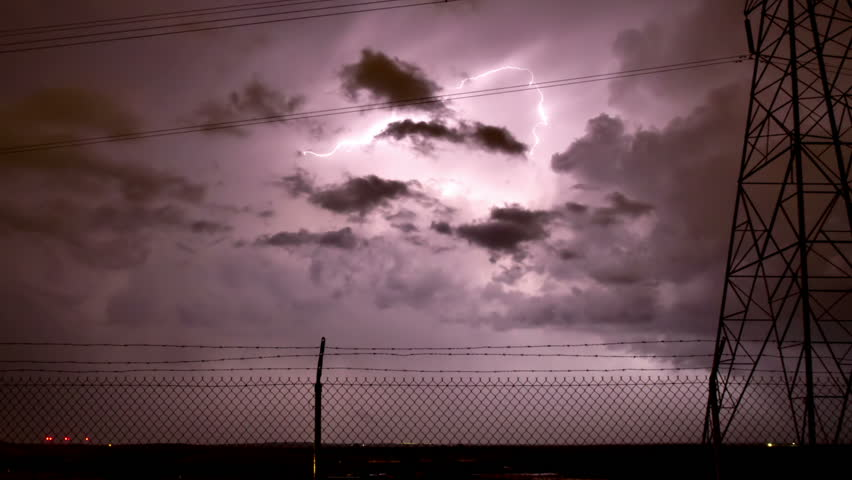 Huge thunderstorm storm with extensive lightning, framed by an electrical tower