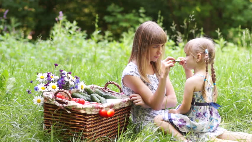 Mother and daughter with vegetables in nature. They eating cucumbers