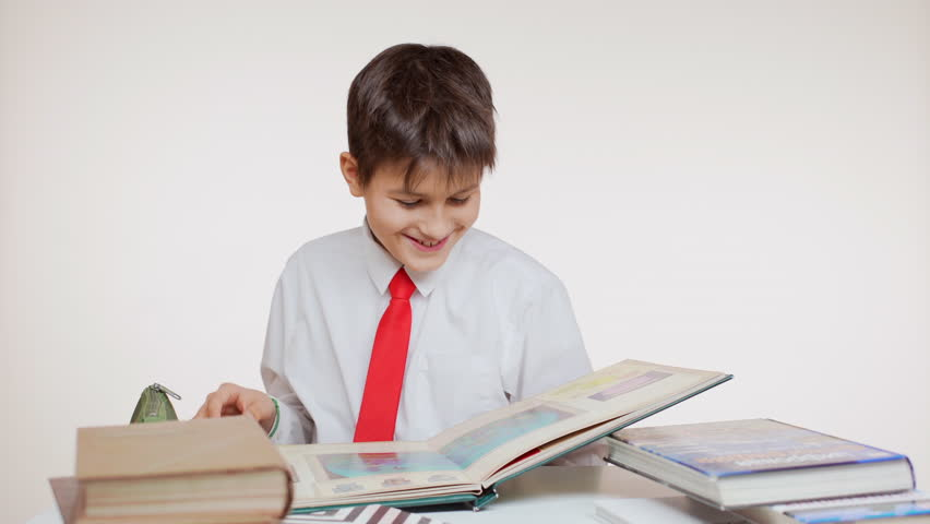 Smiling Caucasian school kid folding pages of big atlas sitting at table on white background | Shutterstock HD Video #24240554