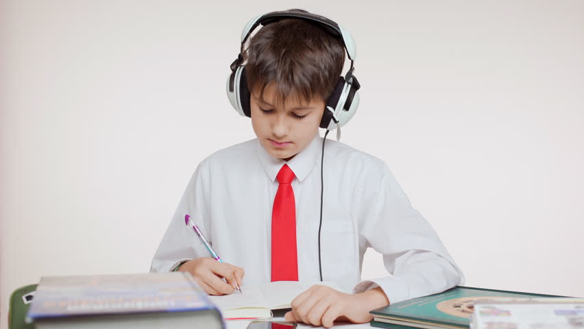 Young concentrated Caucasian school kid in red tie sitting at table wiritng listening music through headphones on white background | Shutterstock HD Video #24240563