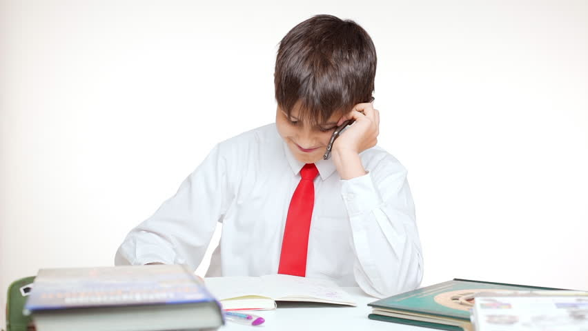 Young Caucasian school kid in red tie sitting at table writing talking on mobile phone on white background in slowmotion | Shutterstock HD Video #24255134