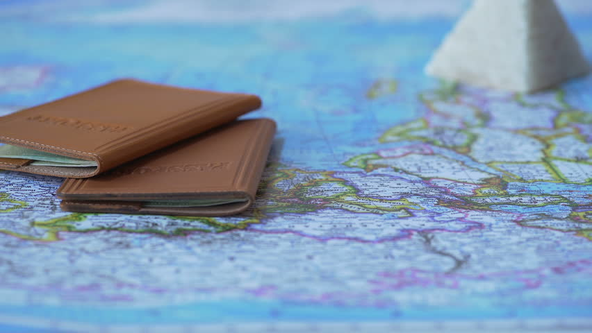 Foreign passports and souvenirs from summer vacation on map, travel by car | Shutterstock HD Video #24260408
