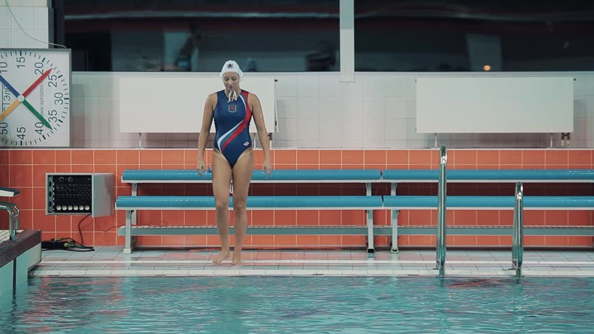 Girl water polo player in white cap blue swimsuit with russian symbols dip into sports inside swim pool   Shutterstock HD Video #24273071