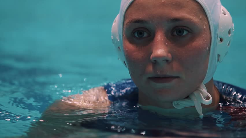Female water polo sport player face gray eyes in white cap blue swimsuit floating in swimming pool   Shutterstock HD Video #24273080