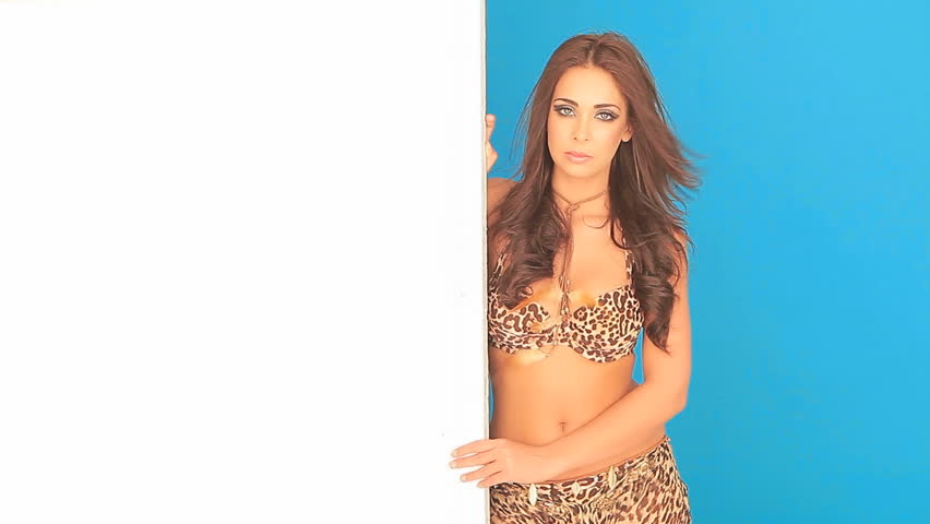 Stunning young woman in an animal print bikini holding a blank placard from the side ready for your advertisement or text - HD stock footage clip