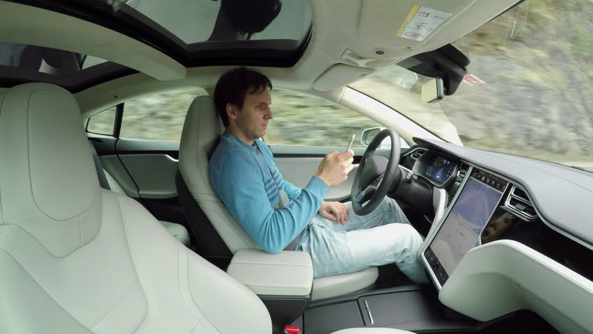 Male driver writing messages on smartphone sitting behind self-driving steering wheel in autonomous autopilot driverless electric car traveling along the countryside road. Man texting in the vehicle | Shutterstock HD Video #24395867