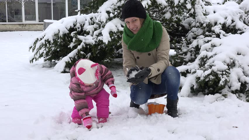 Woman with daughter throw snowballs. Happy family girls. Snowflakes snow falling. Static closeup shot. 4K UHD | Shutterstock HD Video #24494453