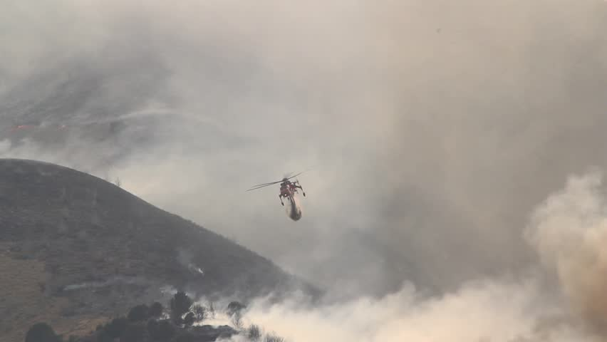 A helicopter battles a gigantic wildfire on a dry mountainside, dropping hundreds of gallons of water on the flames. | Shutterstock HD Video #2450501