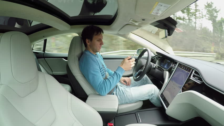 Male driver writing messages on smartphone sitting behind self-driving steering wheel in autonomous autopilot driverless electric car traveling along the countryside road. Man texting in the vehicle | Shutterstock HD Video #24508484