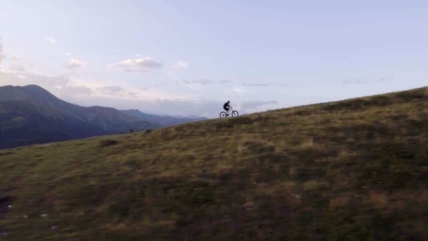 biker trail ride on offroad path by mountain bike in summer sunny day, approaching sunset or sunrise dawn or dusk 4k aerial drone follow flight wide shot  #24644096