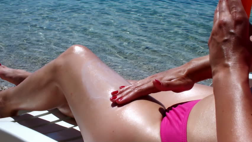 pretty woman applying sun tan lotion on the beach - HD stock video clip