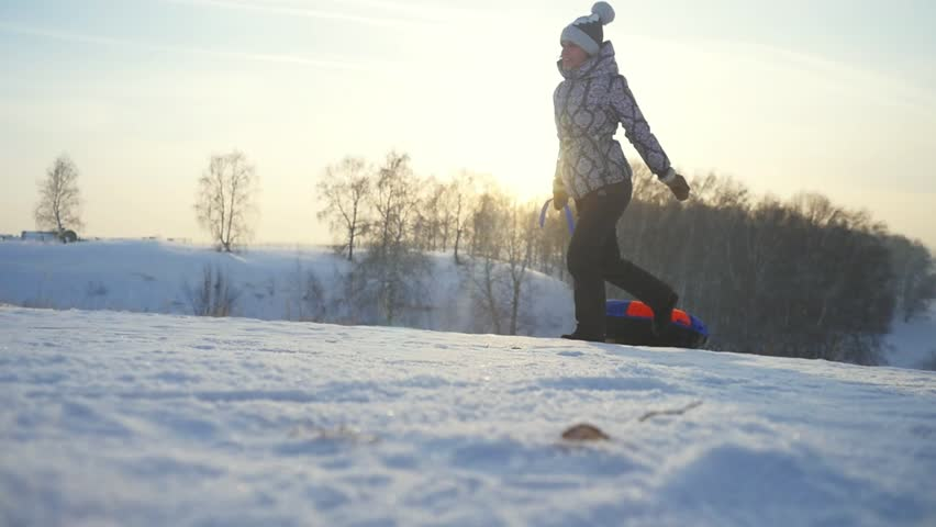 Young woman tobogganing running in the mountains through the sun in slow motion in winter have a good time. 1920x1080 | Shutterstock HD Video #24956423