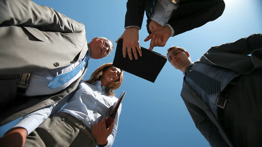 Business people viewed from below greeting each other shaking hands and collaborating