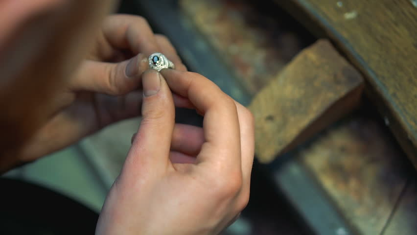 Jeweler holds a finished silver ring in his hands and continues polishing | Shutterstock HD Video #24995762