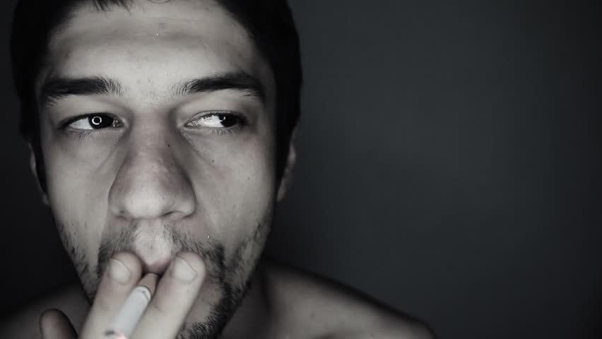 Young man smoking a cigarette looking at camera