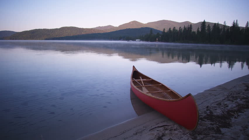 Red Canoe On The Shore Of Priest Lake At Sunrise. Mountains And Trees Reflected In The ...