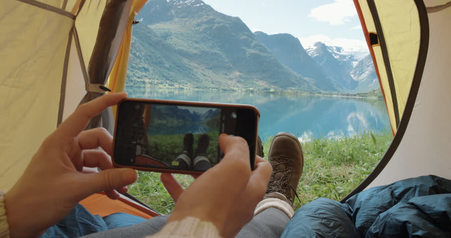 Camping woman lying in tent taking photo of feet with smart phone Close up of Girl wearing hiking boots relaxing on vacation POV Norway | Shutterstock HD Video #25065458