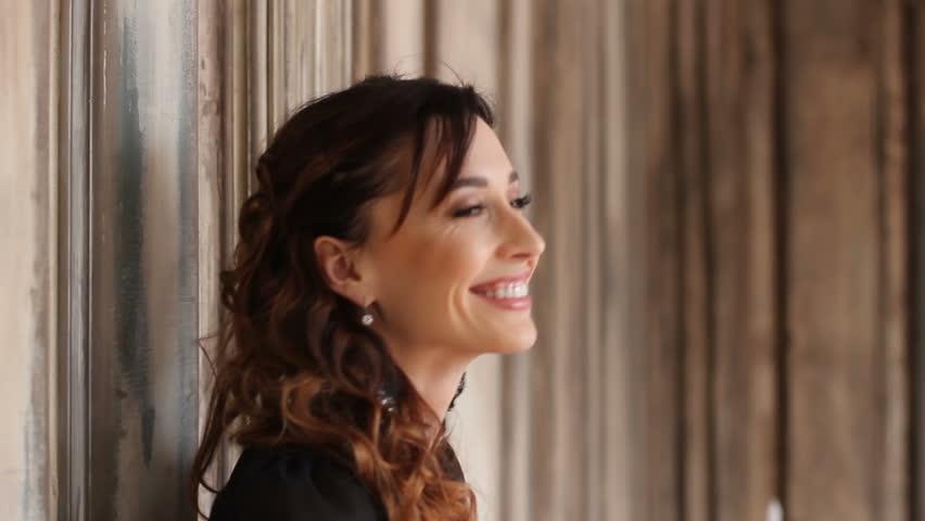 Portrait of laughing pretty brunette woman near art wall | Shutterstock HD Video #25081325