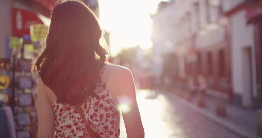 Rear view woman walking through European street at sunset wearing pretty floral summer dress sunshine lens flare confident girl exploring local Paris enjoying holiday travel vacation adventure | Shutterstock HD Video #25098551