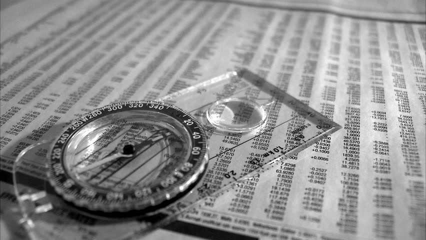 Compass needle on a stock exchange list in a paper. - HD stock footage clip