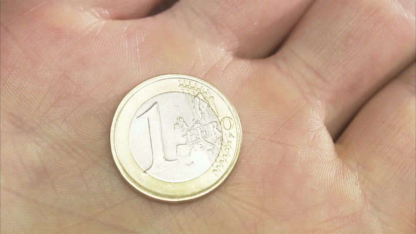 A coin in a hand, on stock exchange list in a paper. - HD stock video clip