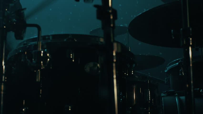 Drummer man playing drums under snow falling. Close up of drumming man snowflakes falling. Man drummer silhouette. Music drums set. Man drum player. Drummer playing drums