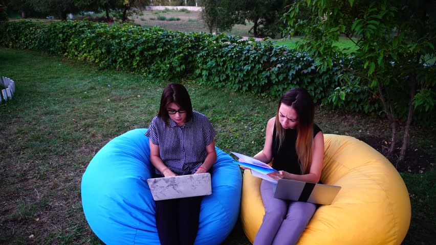Two Educated Young Women Work at Computer, Review Schedules and Business Documentation, Successfully Complete Work Day and Stretch Out Sitting in Soft Colored Armchairs in Open Air on Warm Summer | Shutterstock HD Video #25129205