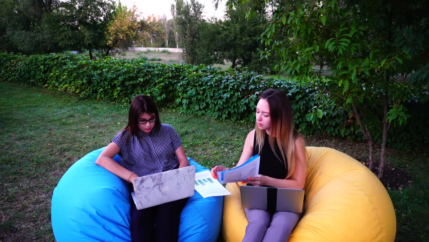 Two Educated Sales Specialist Girls Compare Reports and Discuss Working Moments, Successfully Performed Work and Are Stretched Sitting in Soft Colored Armchairs in Open Air on Warm Summer Day. Girl | Shutterstock HD Video #25129214