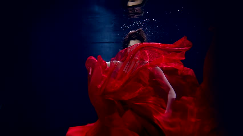 Flight in weightlessness of the underwater world of the young beautiful girl in elegant red dress. | Shutterstock HD Video #25144433