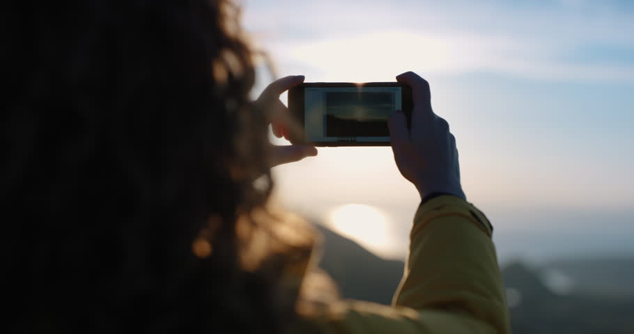 Close up Woman taking photo of sunset with smartphone Girl photographing sunrise picture of ocean view with soft light lens flare landscape nature background enjoying vacation travel adventure | Shutterstock HD Video #25169543