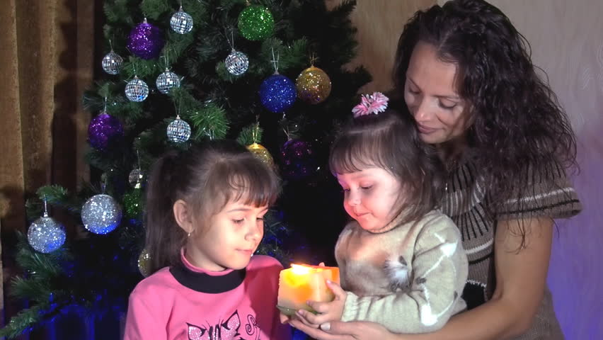 Family under a Christmas tree with a candle. Mom and daughters at the Christmas tree with a candle. A small child with a burning candle. Slow motion. | Shutterstock HD Video #25190855