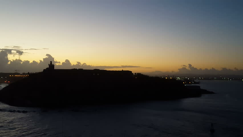 Establishing shot-Passing the dark silhouette of San Felipe Del Morro Fortress and lighthouse San Juan, Puerto Rico as first light of day lights the morning sky | Shutterstock HD Video #25220357