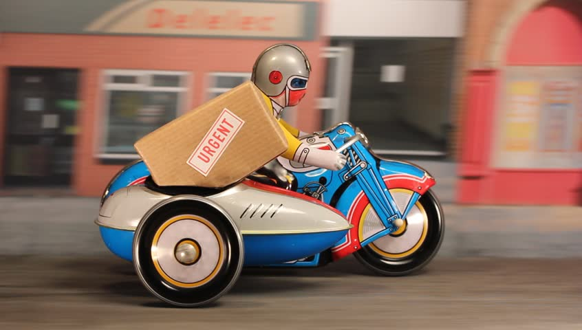 Tin toy delivery motorbike and sidecar speeding along a city street with an urgent parcel.