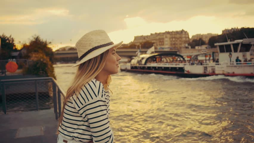Woman tourist in Paris. Traveller female in hat relaxing, beautiful sunset near the Seine river.    Shutterstock HD Video #25288568