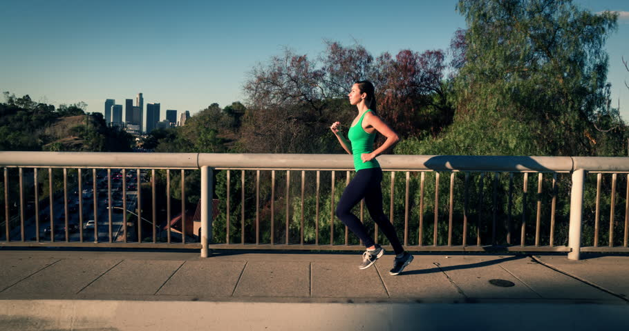 Athletic Woman Working Out. Jogging across a bridge. Trees, Sun and city can be seen in the background. Slow Motion. | Shutterstock HD Video #25296920