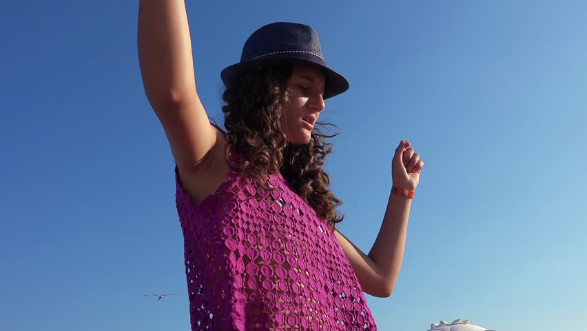 Girl with hat and curly hair dancing at party on the beach | Shutterstock HD Video #25302194