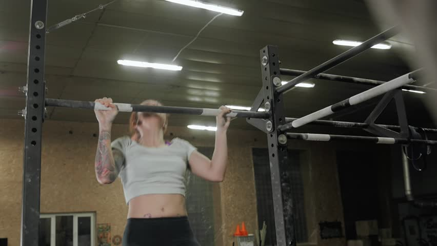 Fitness, sport, exercising lifestyle - Fit woman doing exercises on horizontal bar in cross fit gym | Shutterstock HD Video #25331822
