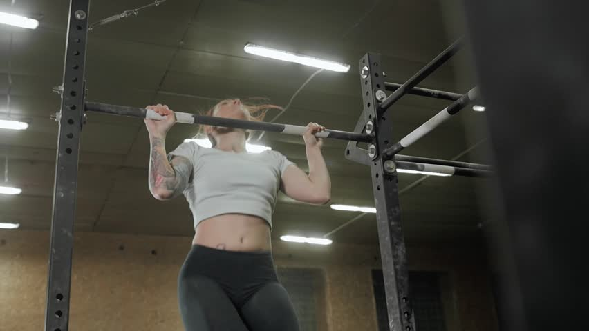 Fitness, sport, exercising lifestyle - Fit woman doing exercises on horizontal bar in cross fit gym | Shutterstock HD Video #25331831