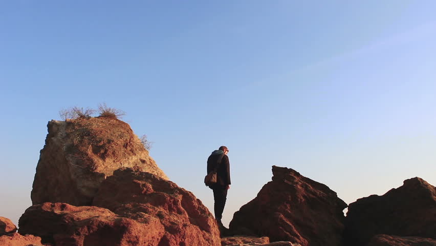 Man standing on stones against the sky #25341020