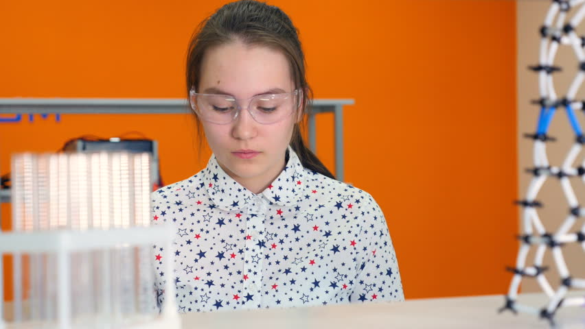 Chemist school girl 10-11 years in glasses mixing chemicals in test tube. | Shutterstock HD Video #25344377