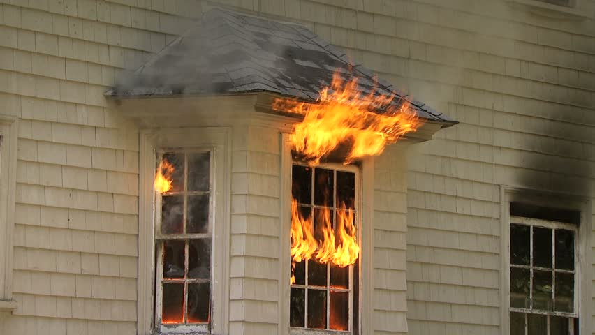 Flames pouring out of window of house on fire - medium shot