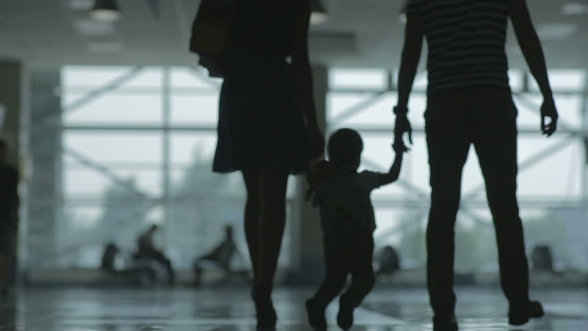 Woman man and child at the airport silhouettes