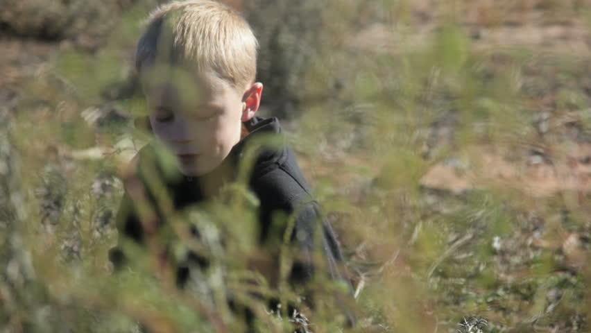 Little boy sitting by himself in desert field - HD stock video clip