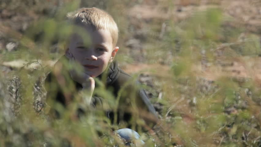 Little boy sitting by himself in desert field - HD stock footage clip