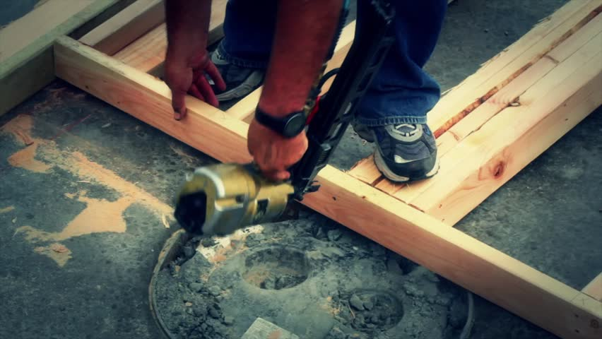 Construction workers using a nail gun to build the walls of a house